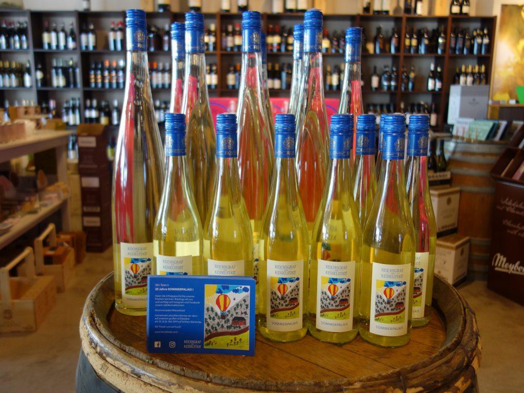 Weißwein-Flaschen vor Regalen